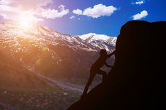 Silhouette of a man to conquer the peak. Mountains against a beautiful sunset royalty free stock photo