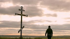 Silhouette man on top of the mountain looking with hope at the Christian Cross. A man making a confession to the cross, background. Concept conceptual black stock video footage