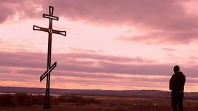 Silhouette man on top of the mountain looking with hope at the Christian Cross. A man making a confession to the cross, background. Concept conceptual black stock video