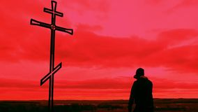 Silhouette man on top of the mountain looking with hope at the Christian Cross. A man making a confession to the cross. Concept conceptual black cross or stock video footage
