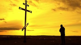 Silhouette man on top of the mountain looking with hope at the Christian Cross. A man making a confession to the cross. Concept conceptual black cross or stock footage