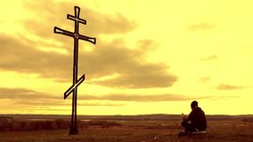 Silhouette man on top of the mountain looking with hope at the Christian Cross. A man making a confession to the cross. Concept conceptual black cross or stock video