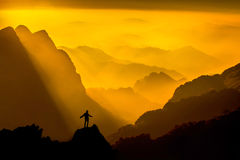 Silhouette of man on top of mountain with sunset. Conceptual sce Royalty Free Stock Image