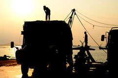Silhouette of man on truck with sunset sky. Worker breaking the ice for fishing boat stock photo