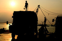 Silhouette of man on truck with sunset sky. Worker breaking the ice for fishing boat royalty free stock photography