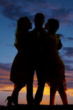 Silhouette man between two women sunset. A silhouette of a men inbetween two women in the outdoors royalty free stock photography