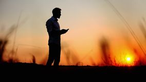 Silhouette of man use mobile phone against the sun in evening time on sunset stock footage