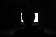 Silhouette of man using blank screen laptop in dark room. Silhouette of young man sitting at the table and using blank screen laptop in dark room Stock Image