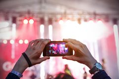 Silhouette of a man using smartphone to take a video at a concert. Royalty Free Stock Photo