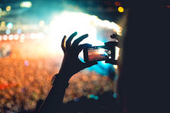 Silhouette of man using smartphone to take a video at a concert. Modern lifestyle with hipster taking pictures and videos Stock Photos