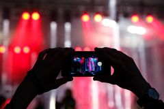 Silhouette of a man using smartphone to take a video at a concert. Stock Photography