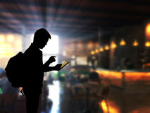 Silhouette man using tablet computer with blue coffee shop backg Royalty Free Stock Images