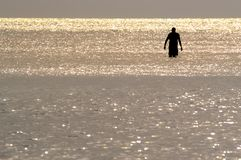 A Silhouette of a man wading in the ocean. stock photo