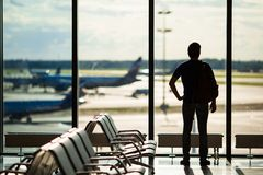 Silhouette of a man waiting to board a flight in. Silhouette of a man waiting to board a flight Royalty Free Stock Photo