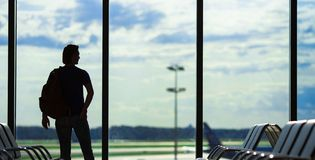 Silhouette of a man waiting to board a flight in Stock Image