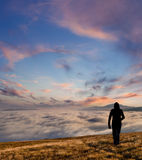 Silhouette of the man walking above the clouds Stock Photos
