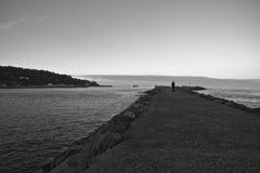 Silhouette of man walking on breakwater in sunset by atlantic ocean Royalty Free Stock Photo