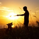 Silhouette of a man walking with a dog on the field at sunset, boy playing with pet outdoors, concept of happy pastime and friends royalty free stock photo