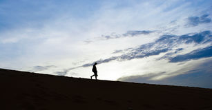 Silhouette man walking down desert with clouds. Blue sky background in the morning Royalty Free Stock Image