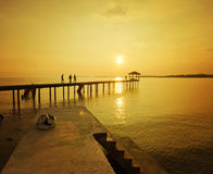 Silhouette of man walking at the jetty during golden sunset Royalty Free Stock Photography