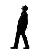 Silhouette man walking musing looking up. Silhouette caucasian business man walking musing looking up expressing behavior full length on studio isolated white stock photo