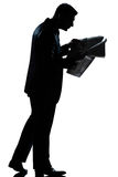Silhouette man walking newspaper full length Stock Images