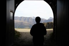 The silhouette of man walking out from the tunnel. After across the mountain tunnel of glacier, at the gate of the tunnel, one man walking out, which was the royalty free stock image