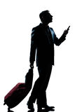 Silhouette man walking on the phone full length. One caucasian business traveler man walking on the phone with suitcase full length silhouette in studio isolated royalty free stock image