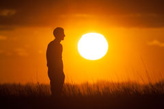 Silhouette of a Man Watching the Sunset Stock Images