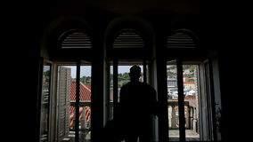 Silhouette of a man wear his jacket on the balcony stock footage