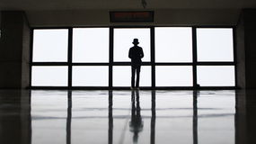 Silhouette of Man Wearing Hat Standing Near Window during Daytime Royalty Free Stock Photo