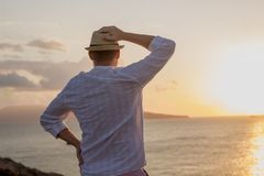 Silhouette of a man in white clothes and a hat stands with his back in the golden rays of the sun against the background of a dawn. Over the sea. The back of a Stock Photography