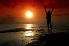Silhouette of a man who jumped. Into the direction of the sun photographed before sunrise Stock Photography