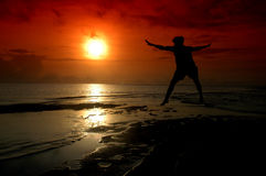 Silhouette of a man who jumped into the sun. Silhouette of a man who jumped into the direction of the sun photographed before sunrise Stock Photos