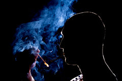 Silhouette of man who lights the cigarette in the dark Royalty Free Stock Photo