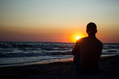 Silhouette of a man who sits on the sand near the sea, in the rays of the setting sun near the sea. place under the text, relax on. Silhouette of a young man royalty free stock images