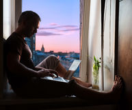 Silhouette of man on window sill with laptop Royalty Free Stock Photos