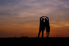 Silhouette man and woman with beautiful the sky at sunset.Backg Stock Photography