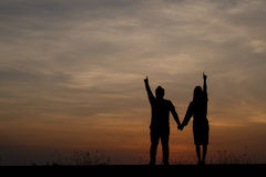Silhouette man and woman with beautiful the sky at sunset.Backg Stock Photo