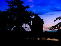 Silhouette man and woman endearment love romantic. Silhouette man and woman endearment love romantic near river and sky in twilight time royalty free stock photography