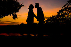 Silhouette man and woman endearment love romantic. Silhouette man and woman endearment love romantic near river and sky in twilight time royalty free stock photo