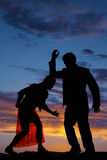 Silhouette man woman facing each other elbow on head. A silhouette of a women bent over with her man's arm resting on her head royalty free stock image