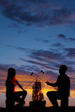 Silhouette man and woman hold up marshmallows. A silhouette of a women and men in the outdoors roasting marshmallows over a fire Royalty Free Stock Photography