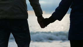 Silhouette of a man and a woman holding their hands against the background of the sea stock footage