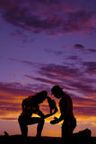 Silhouette of man and woman kneeling heads down. A silhouette of a cowgirl kneeling down with the cowboy leaning down praying Stock Images