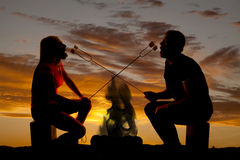 Silhouette man and woman with roasted marshmallows Royalty Free Stock Image