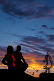 Silhouette man and woman roasting some marshmallows on fire. A silhouette of a couple in the outdoors roasting marshmallows Stock Photography