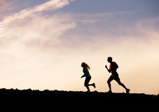 Silhouette of man and woman running jogging together into sunset Stock Images