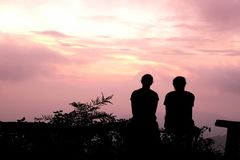 Silhouette Man and woman sitting watch the evening sky at purple sunset Royalty Free Stock Photo