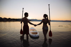 Silhouette of man, woman with sup surf and paddle at the ocean. Concept lifestyle, sport, love Stock Photo